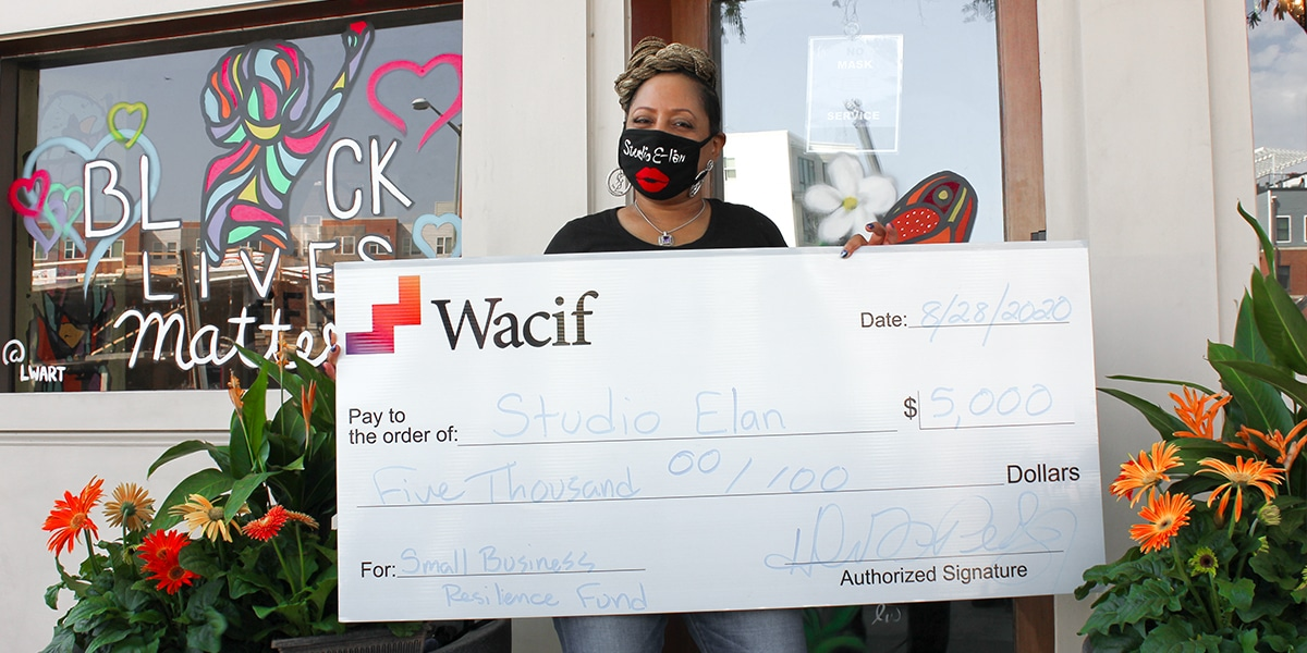 Photograph of woman of color entrepreneur holding a check from Wacif for $5,000